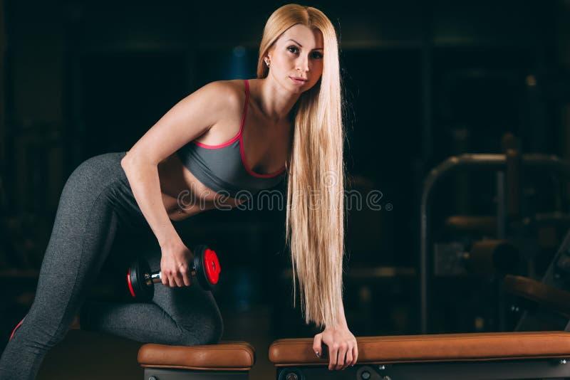 La mujer atlética brutal que bombea para arriba muscles con pesas de gimnasia en gimnasio fotos de archivo