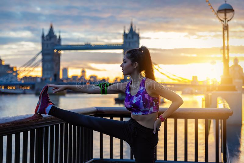 La mujer atlética de la ciudad hace sus estiramientos delante del puente de la torre en Londres fotografía de archivo libre de regalías