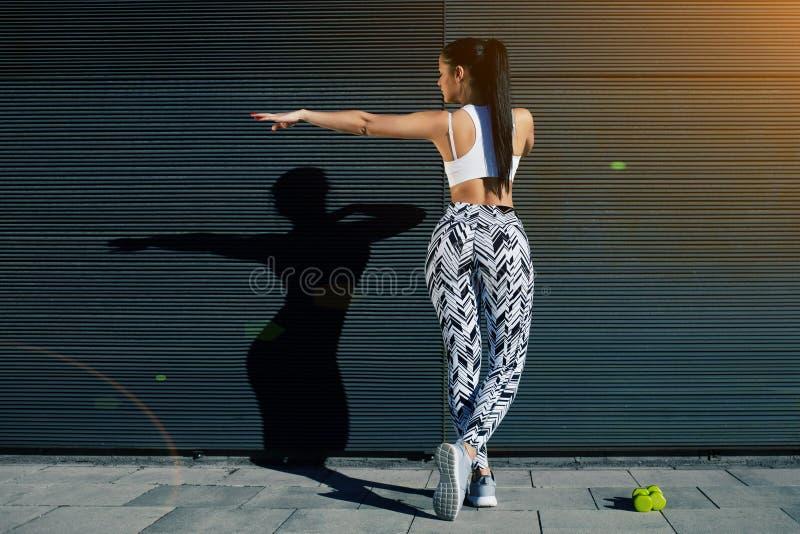 La mujer atlética de la visión trasera con la figura perfecta y las nalgas forman el ejercicio contra la pared con el espacio de  foto de archivo