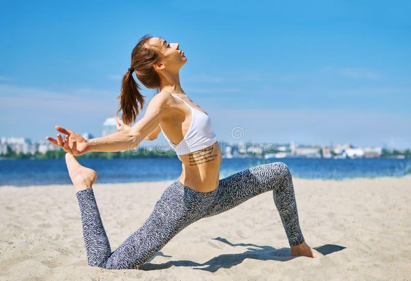 La mujer atlética delgada joven hace ejercicios de la yoga y estirar en la playa de la arena con el fondo de la ciudad Forma de v fotos de archivo libres de regalías