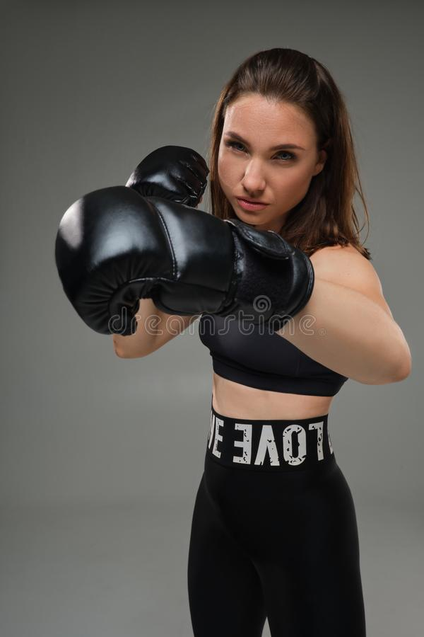 La mujer atlética en guantes de boxeo está practicando karate en estudio imágenes de archivo libres de regalías