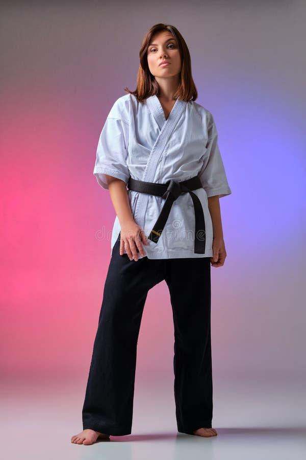 La mujer atlética en kimono tradicional está practicando karate en estudio imagenes de archivo