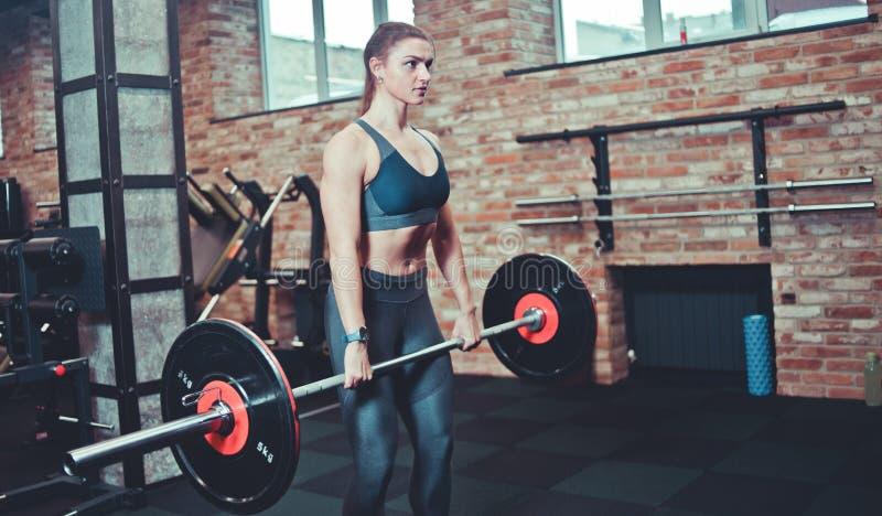 La mujer atlética en ropa de deportes sostiene un barbell pesado imagen de archivo libre de regalías