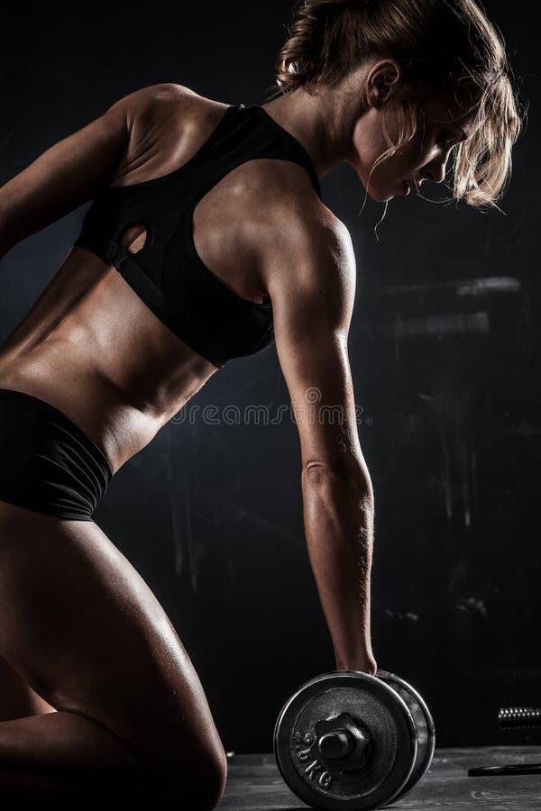 La mujer atlética hermosa hace ejercicios con pesas de gimnasia imagen de archivo