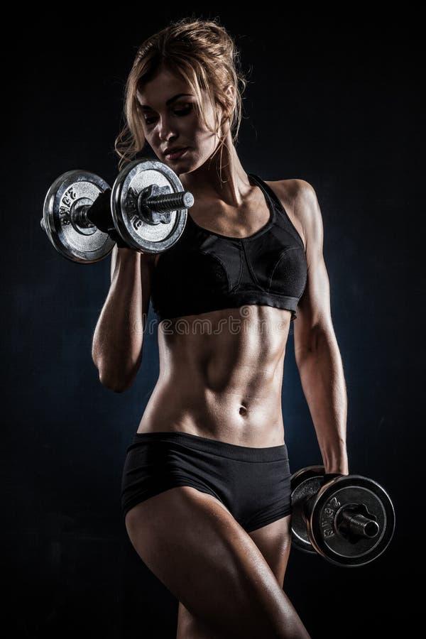 La mujer atlética hermosa hace ejercicios con pesas de gimnasia foto de archivo