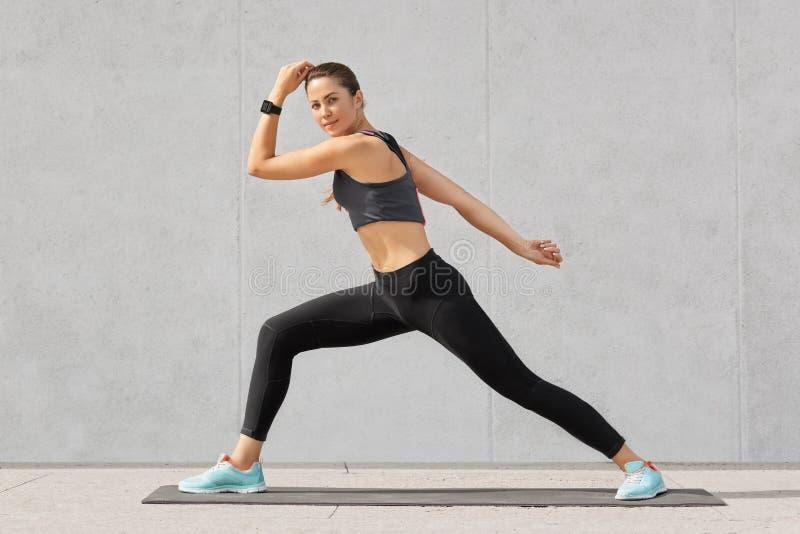 La mujer atlética practica yoga, hace pasos amplios, muestra buena flexibilidad, presenta contra el fondo gris, vestido en sports imagen de archivo