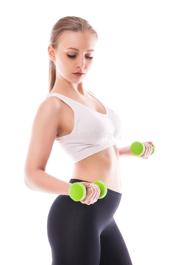 La mujer atlética que bombea para arriba muscles con pesas de gimnasia imagen de archivo libre de regalías