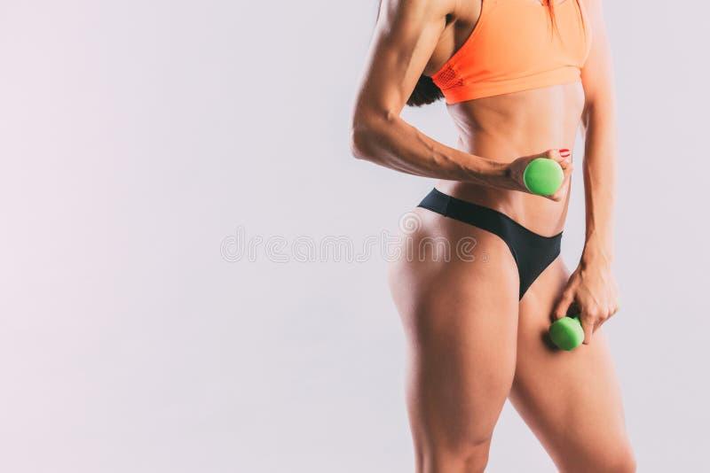 La mujer atlética que bombea para arriba muscles con pesas de gimnasia fotografía de archivo