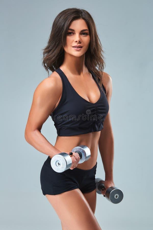 La mujer atlética que bombea para arriba muscles con pesas de gimnasia en fondo gris fotografía de archivo