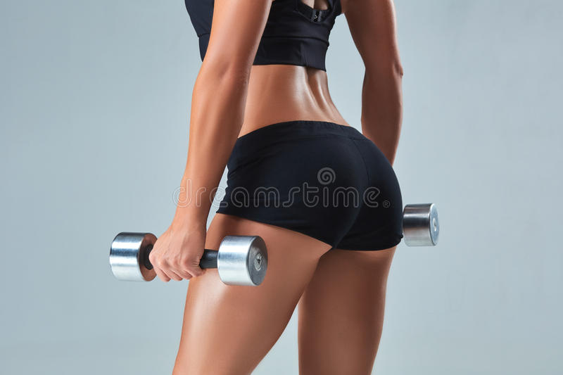 La mujer atlética que bombea para arriba muscles con pesas de gimnasia en fondo gris imagenes de archivo