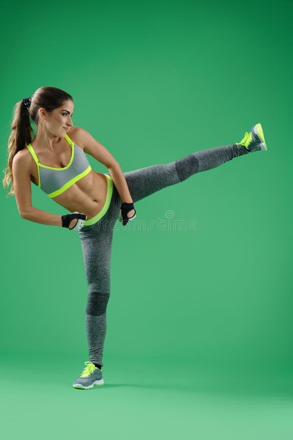 La mujer atlética que entrena a su alto golpea adentro el estudio con el pie en backgro verde imagenes de archivo