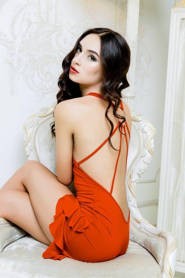 La mujer atractiva con el pelo largo que lleva el vestido rojo con las ondas encrespa el peinado imagen de archivo libre de regalías