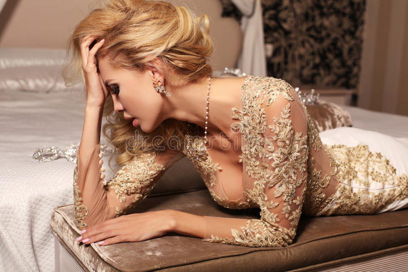 La mujer atractiva con el pelo rubio largo lleva el vestido de boda del cordón de los luxurios y la joya foto de archivo
