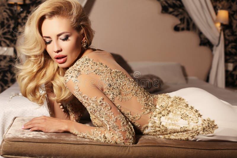La mujer atractiva con el pelo rubio largo lleva el vestido de boda del cordón de los luxurios y la joya fotos de archivo
