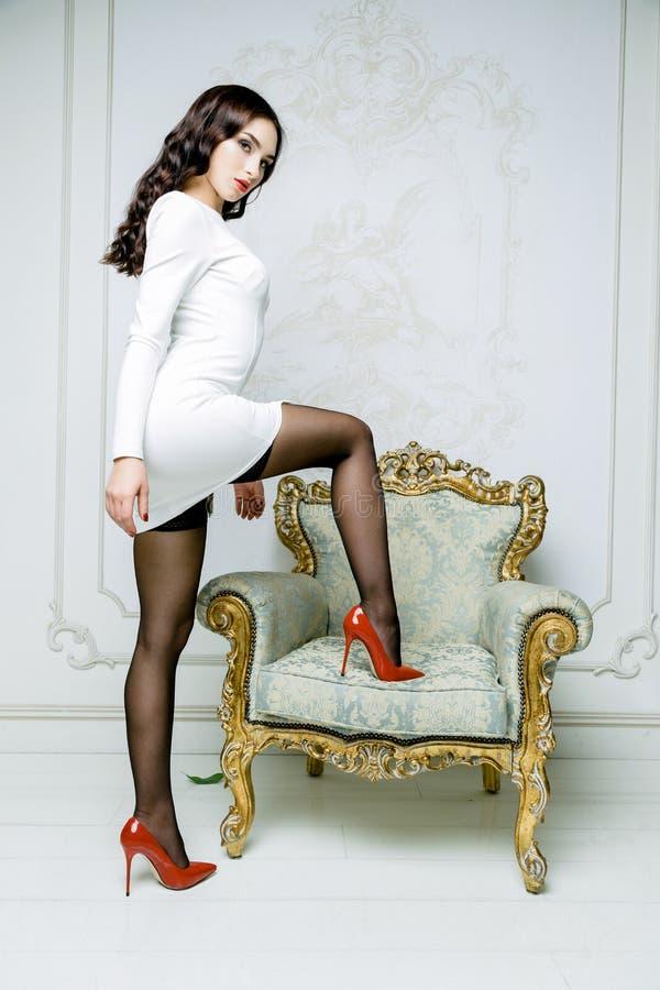 La mujer atractiva con el vestido blanco que lleva del pelo largo con las ondas encrespa el peinado imágenes de archivo libres de regalías