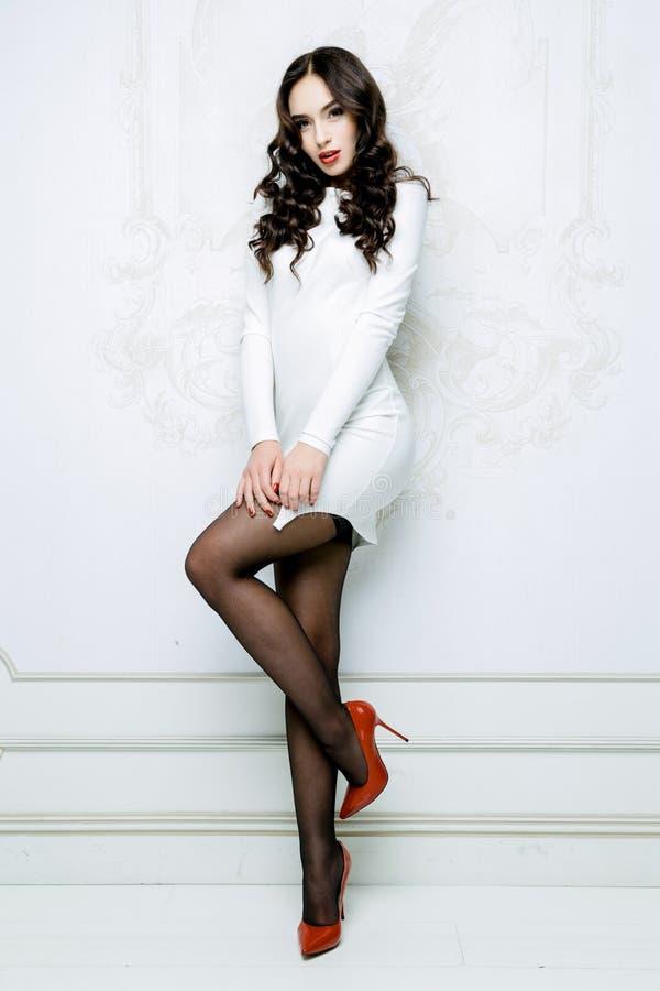 La mujer atractiva con el vestido blanco que lleva del pelo largo con las ondas encrespa el peinado fotos de archivo