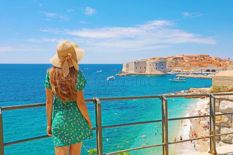 La mujer atractiva con el vestido verde disfruta de la vista de la ciudad vieja de Dubrovnik, Croacia imagen de archivo