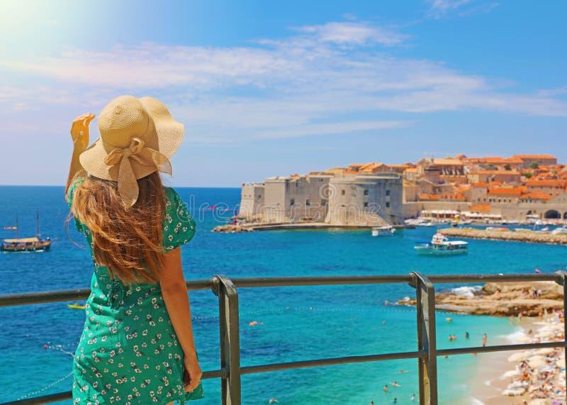 La mujer atractiva con el vestido verde disfruta de la vista de la ciudad vieja de Dubrovnik, Croacia foto de archivo libre de regalías