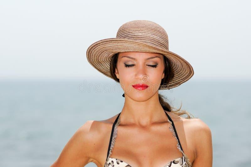 La mujer atractiva con un sombrero del sol en una playa tropical, ojos se cerró foto de archivo