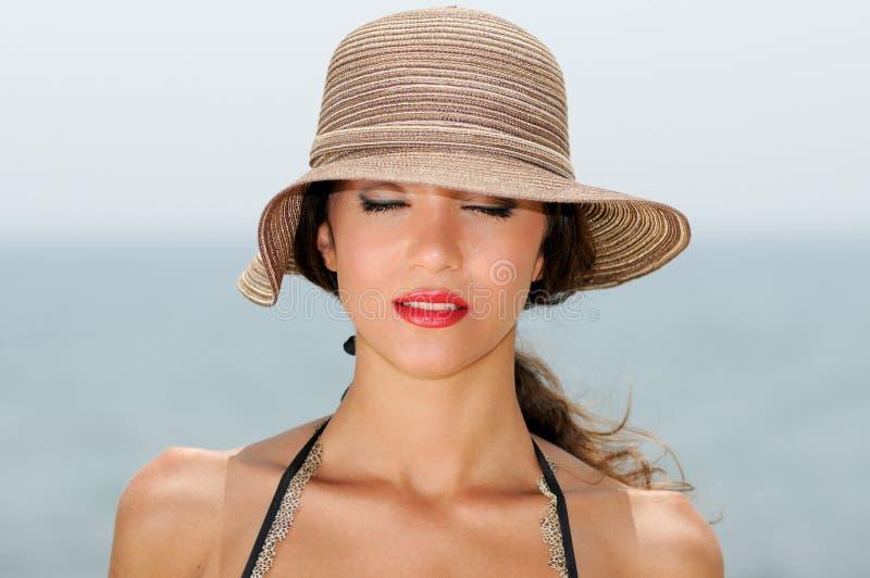 La mujer atractiva con un sombrero del sol en una playa tropical, ojos se cerró foto de archivo libre de regalías