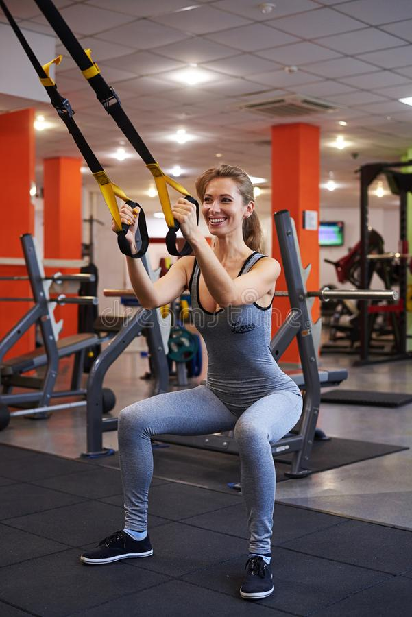 La mujer atractiva del ajuste que trabaja con batalla ropes en el gimnasio foto de archivo libre de regalías