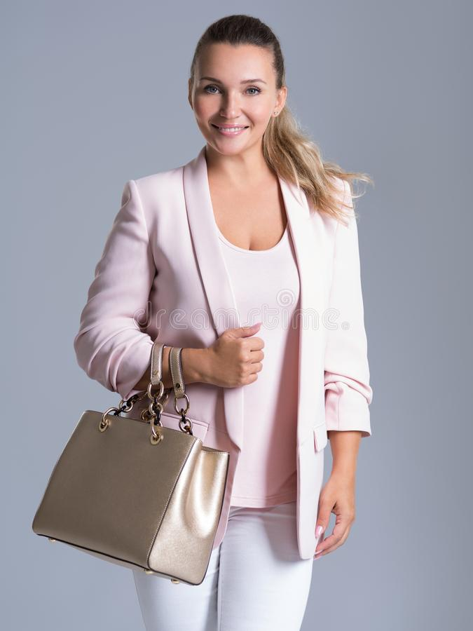 La mujer atractiva del smilinge sostiene el bolso de oro imagenes de archivo