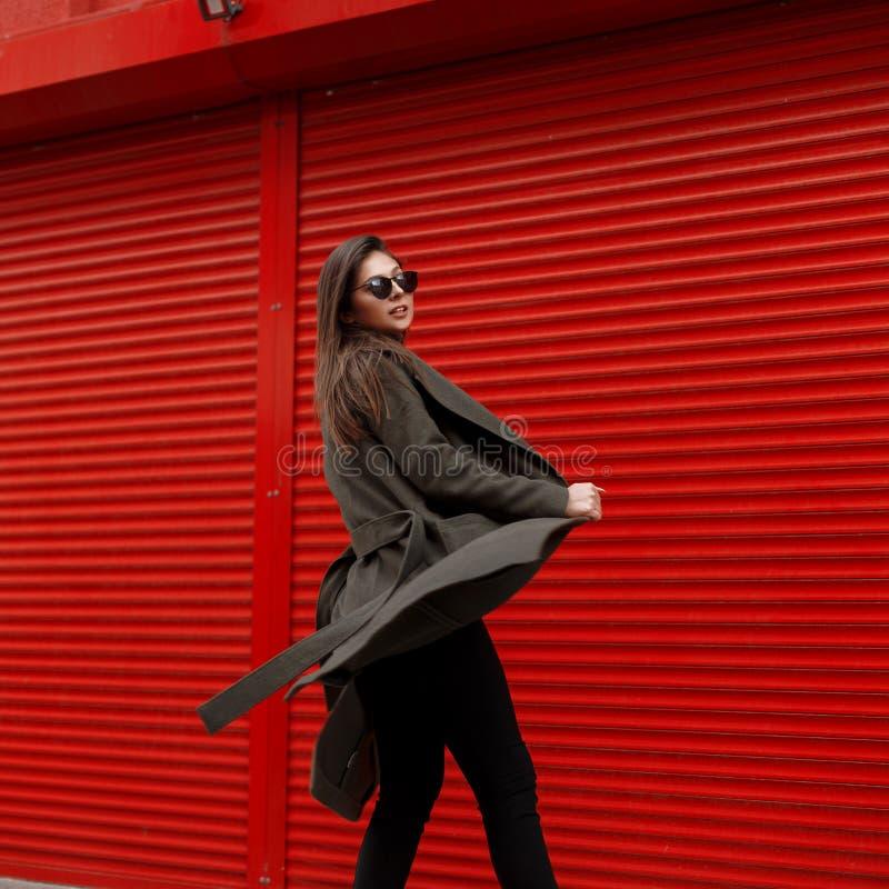 La mujer atractiva delgada joven hermosa con las gafas de sol en el movimiento viste una capa de moda verde cerca de la pared roj imagenes de archivo