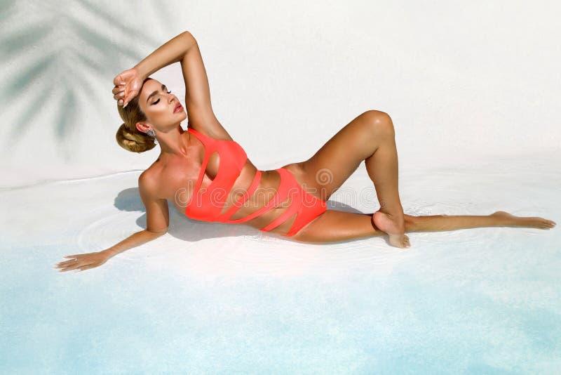 La mujer atractiva elegante en el bikini anaranjado en el cuerpo delgado y bien proporcionado bronceado est? presentando cerca de imagenes de archivo