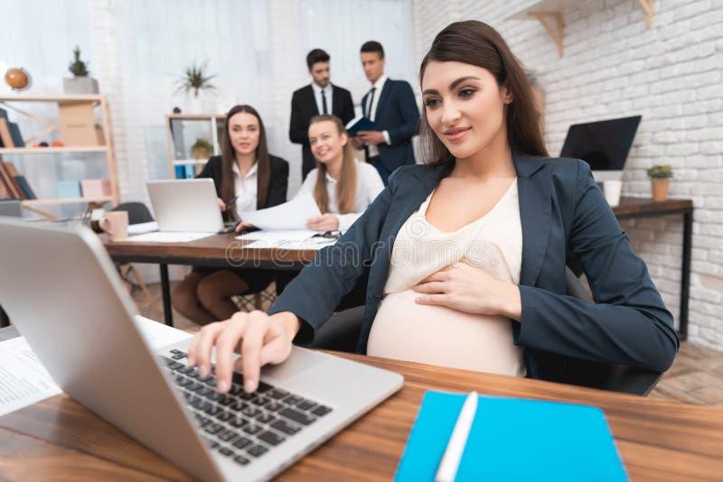 La mujer atractiva embarazada está mecanografiando en telclado numérico del ordenador portátil Embarazo en oficina imagen de archivo