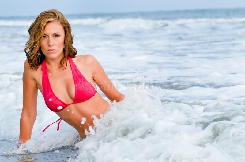 La mujer atractiva en bikiní rojo salpicó por la onda foto de archivo libre de regalías