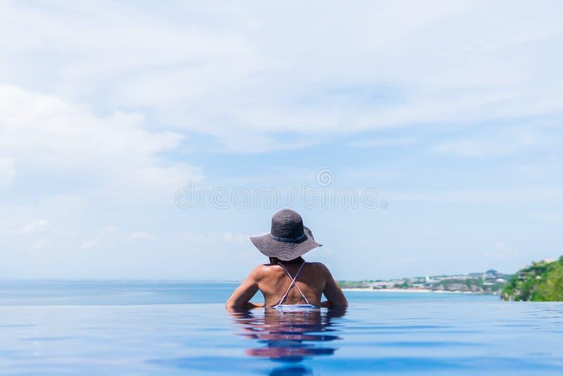 La mujer atractiva en bikini y con el sombrero gris se está relajando en una piscina del infinito foto de archivo libre de regalías