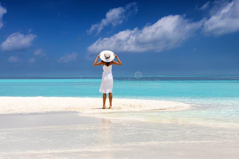 La mujer atractiva en el vestido blanco se coloca en una playa tropical imagen de archivo libre de regalías