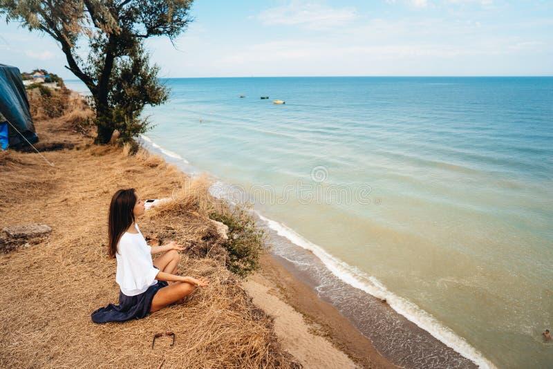 La mujer atractiva en falda y camisa del verano se sienta en la orilla fotografía de archivo libre de regalías