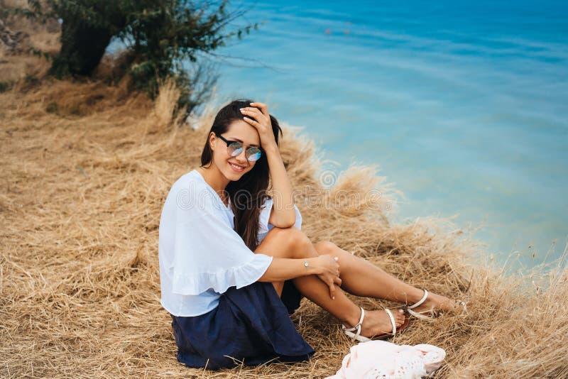 La mujer atractiva en falda y camisa del verano se sienta en la orilla imagenes de archivo