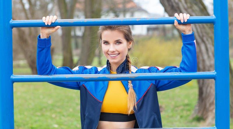 La mujer atractiva en ropa azul del deporte est? ejercitando al aire libre fotografía de archivo