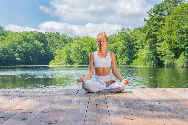 La mujer atractiva está practicando la yoga y la meditación, sentándose en actitud del loto cerca del lago por mañana fotografía de archivo