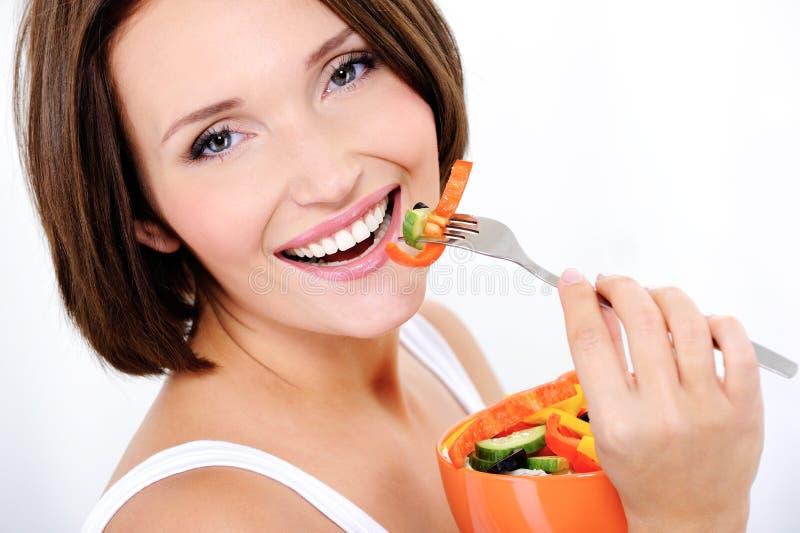 La mujer atractiva feliz come la ensalada vegetal fotos de archivo