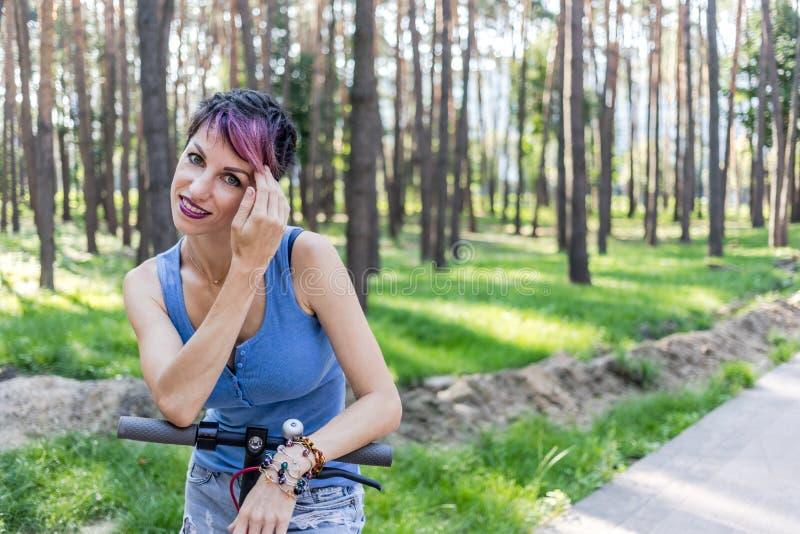 La mujer atractiva fresca con el pelo rosado, goza el montar de una vespa eléctrica fotos de archivo libres de regalías