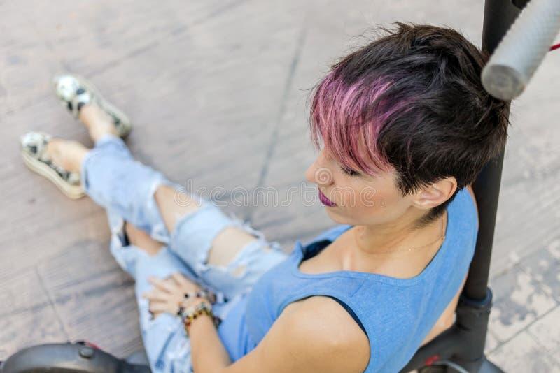 La mujer atractiva fresca con el pelo rosado, goza el montar de una vespa eléctrica foto de archivo libre de regalías