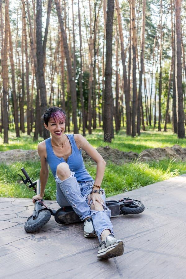 La mujer atractiva fresca con el pelo rosado, goza el montar de una vespa eléctrica imagen de archivo libre de regalías