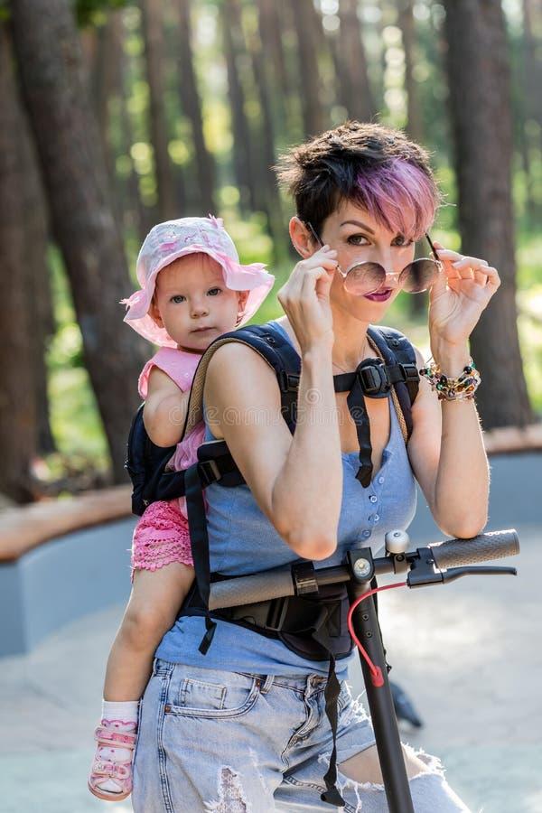 La mujer atractiva fresca goza el montar de una vespa eléctrica con su hija en honda fotos de archivo libres de regalías