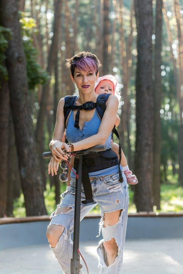 La mujer atractiva fresca goza el montar de una vespa eléctrica con su hija en honda foto de archivo