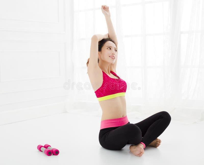 La mujer atractiva hace ejercicio de la yoga en casa imagenes de archivo