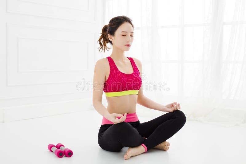 La mujer atractiva hace ejercicio de la yoga en casa foto de archivo
