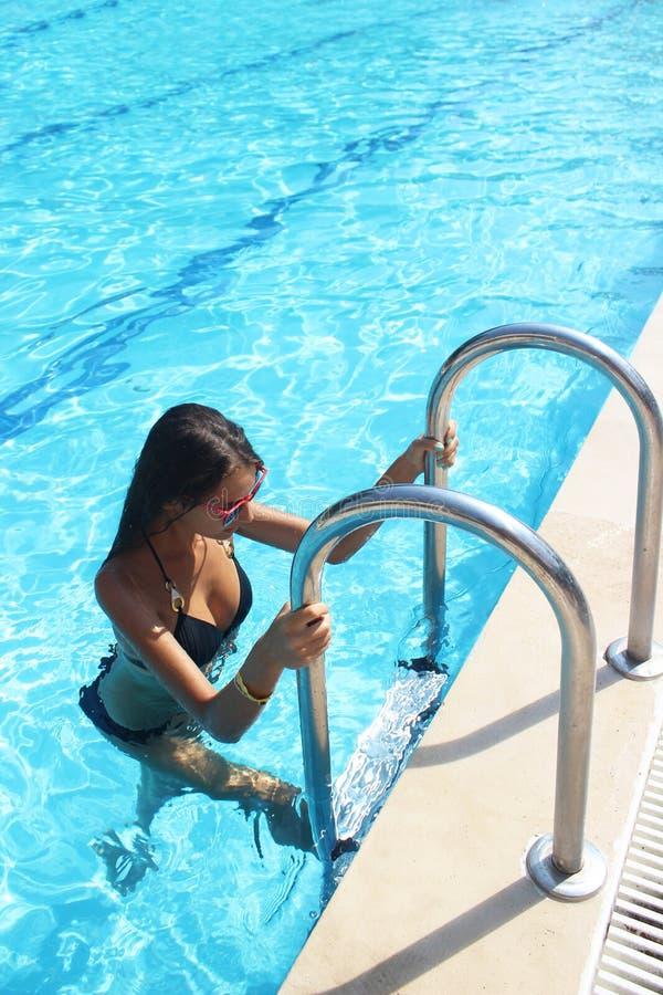 La mujer atractiva hermosa con la figura delgada perfecta con el pelo mojado largo y el bañador que sale de la piscina en las esc foto de archivo