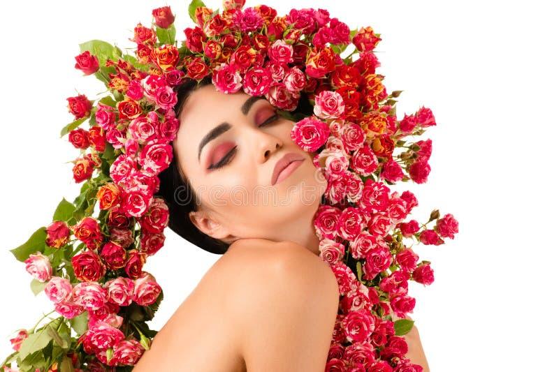 La mujer atractiva hermosa con las rosas rojas florece en la cabeza imagen de archivo libre de regalías