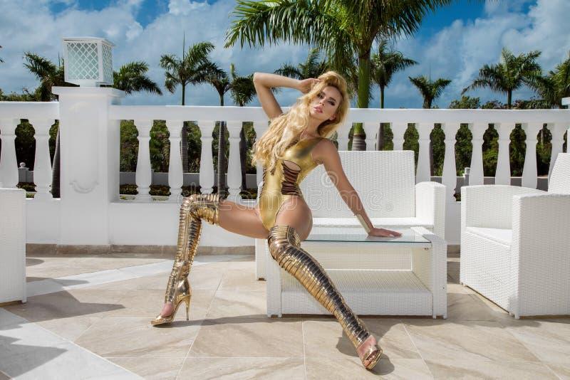 La mujer atractiva hermosa en bikini del oro y oro calza la presentaci?n en el hotel de lujo del Caribe foto de archivo