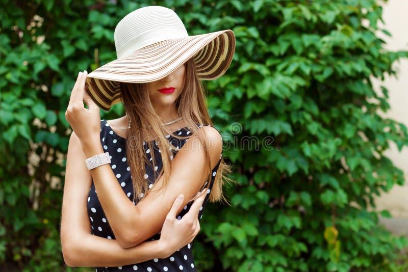 La mujer atractiva hermosa en sombrero elegante con los labios rojos y el lunar negro se visten fotos de archivo libres de regalías