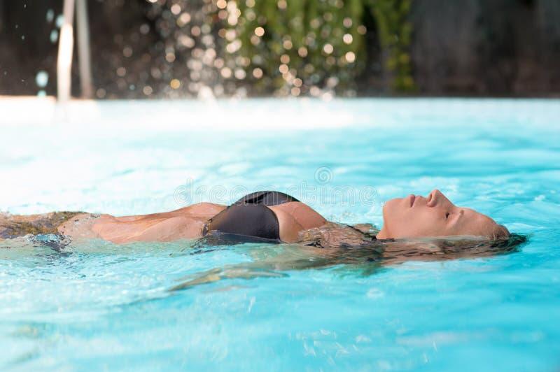 La mujer atractiva hermosa nada en piscina imagenes de archivo