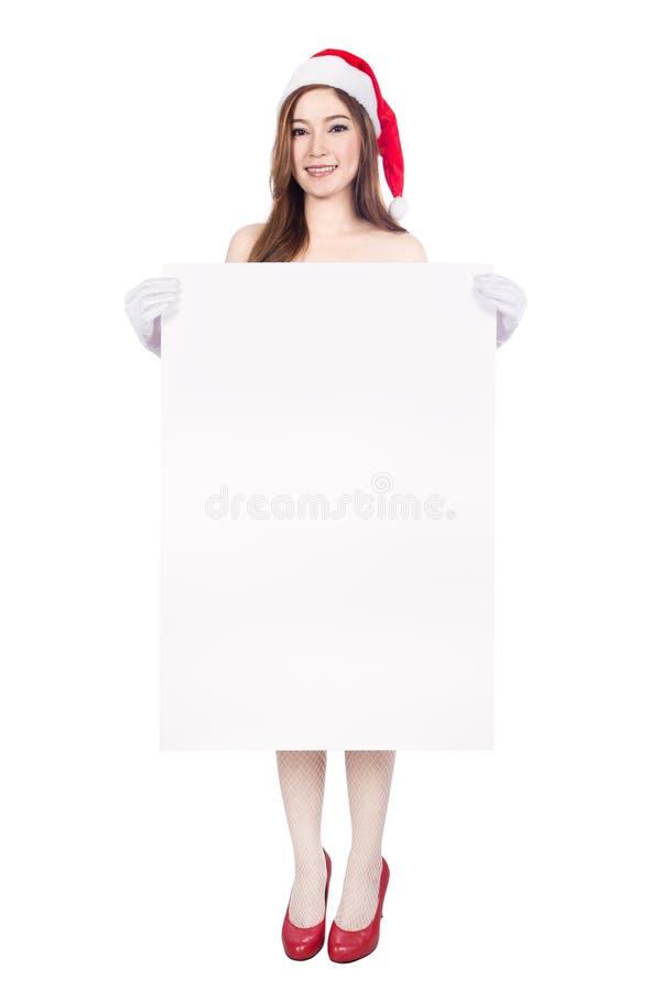 La mujer atractiva hermosa que lleva a Papá Noel viste con la muestra en blanco imagen de archivo